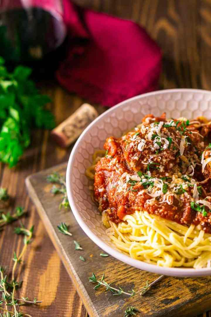 A bowl of Italian meatballs and spaghetti with fresh thyme around it on a wooden board.