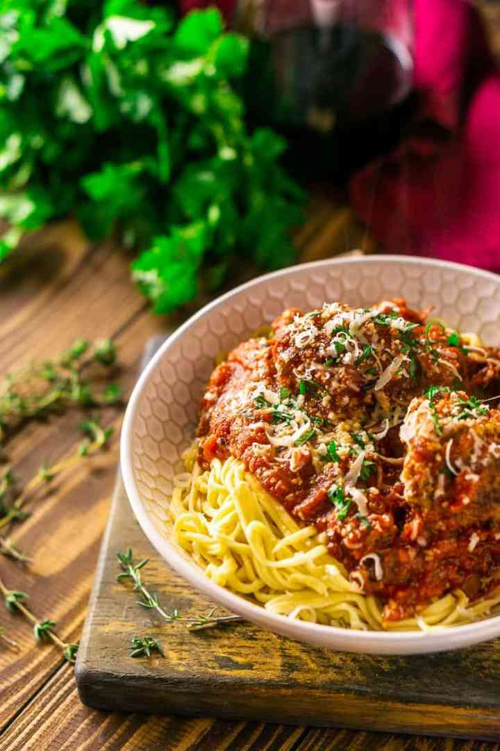 A bowl of Italian meatballs and spaghetti on a wooden tray with fresh parley, thyme and wine in the background.