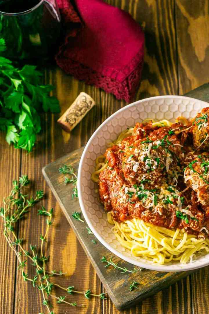 An aerial view of Italian meatballs and spaghetti with fresh herbs around it.