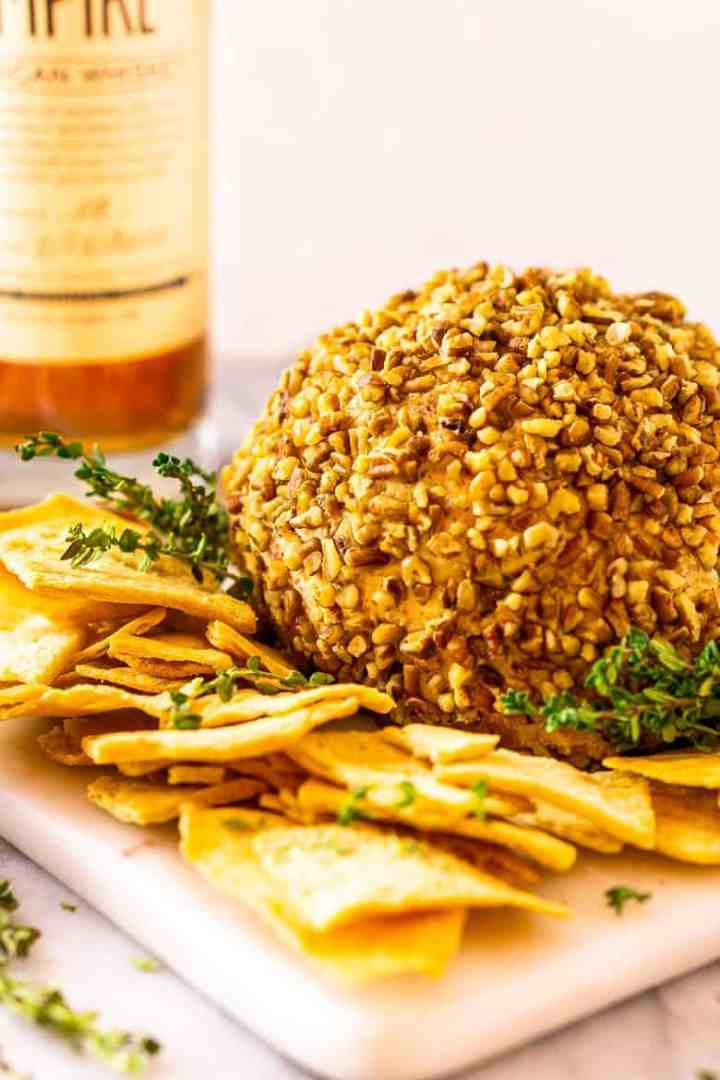 A bourbon bacon jam cheese ball with a bottle of bourbon in the background.