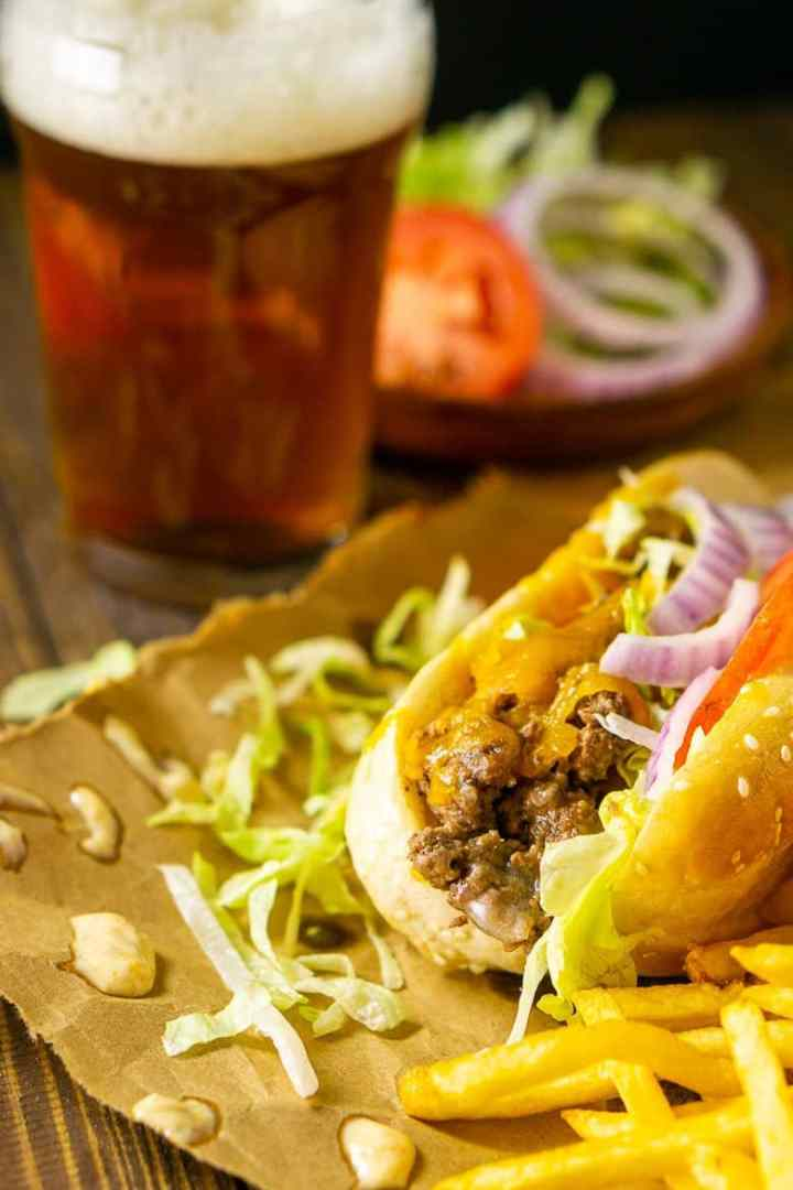 A cheeseburger sub on brown paper with fries on the side and a beer with a plate of toppings.