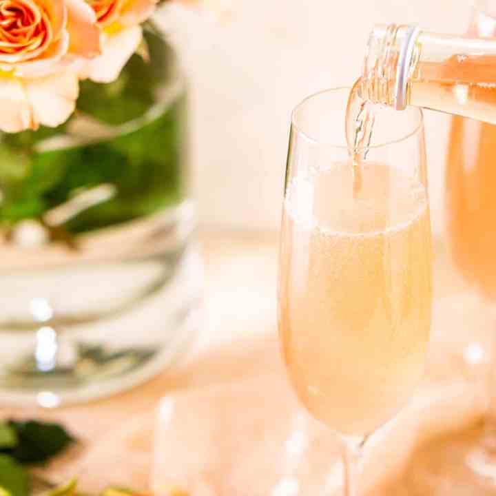 Pouring wine into a rosé French 75 with a bouquet of roses in the background.