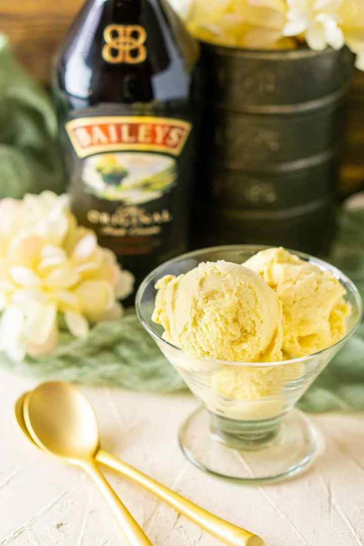 Two gold spoons stacked on top of each other next to a glass cup of Baileys ice cream.