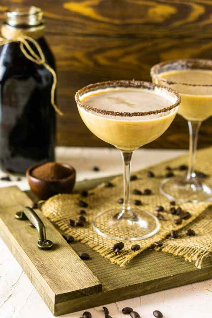 Two Baileys Irish coffee martinis on a wooden platter with coffee beans and a glass bottle of cold-brew coffee.