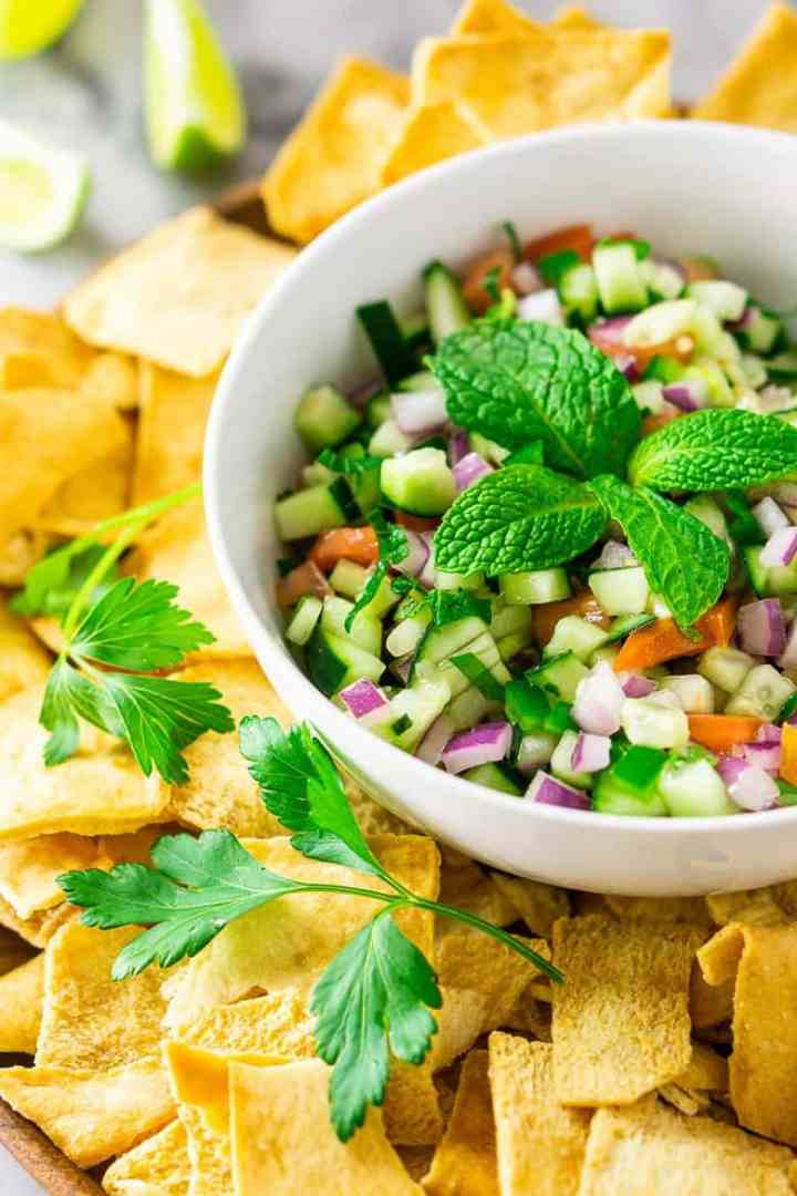 Looking from the side to a bowl of cucumber pico de gallo with herbs, chips and limes.