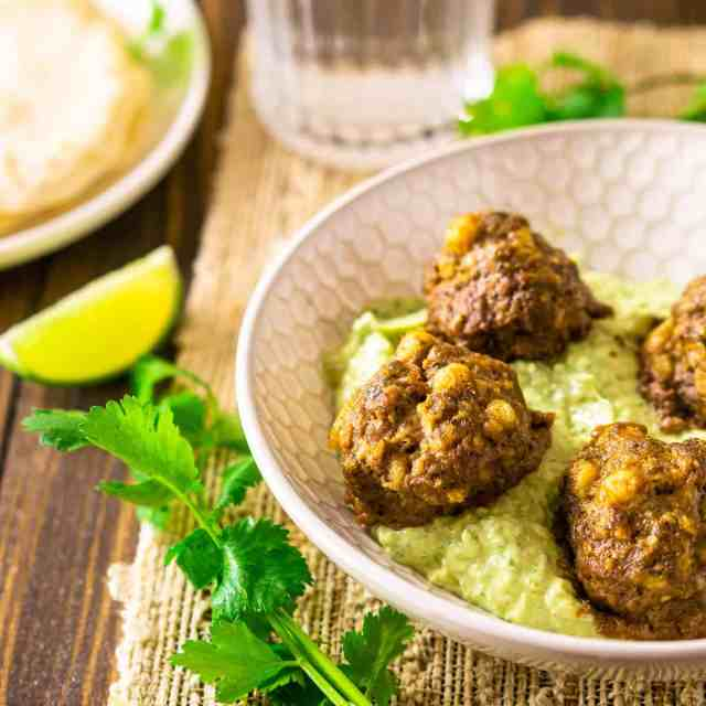Mexican meatballs in a shallow bowl with avocado-crema sauce with cilantro and lime slices.