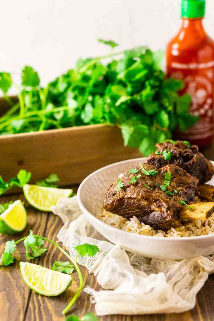 Two braised sriracha short ribs over coconut rice with cilantro, limes and a bottle of sriracha in the background.