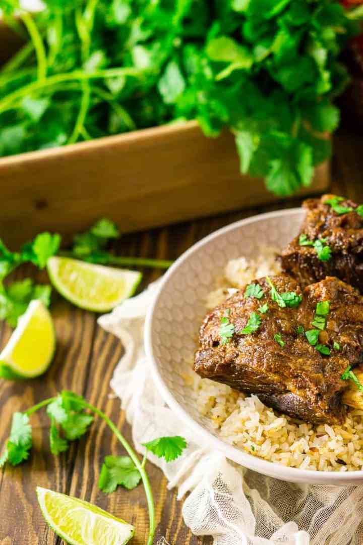 A close-up view of a braised sriracha short rib with cilantro and limes to the side.