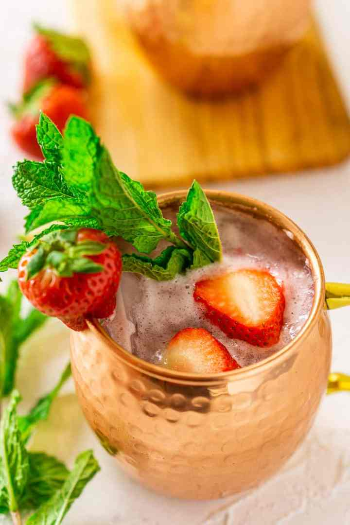 A close-up view of a strawberry-mint Moscow mule with a sprig of mint on the side.
