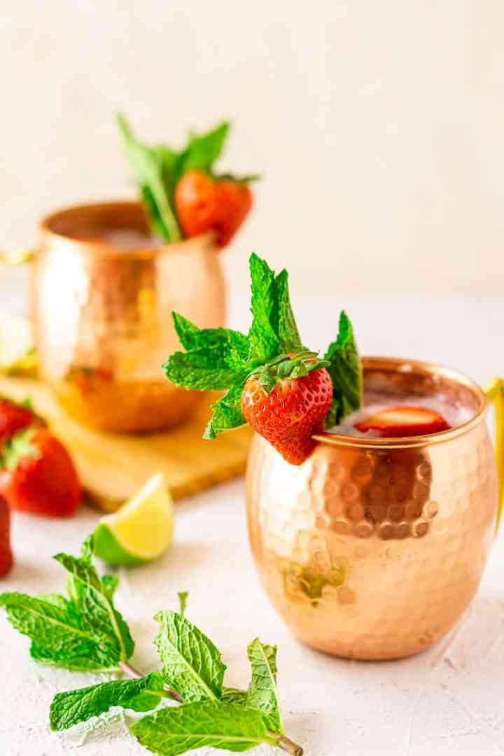 Two strawberry-mint Moscow mules in copper mugs with mint, strawberries and lime slices.