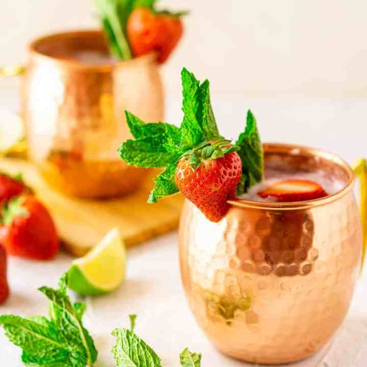Two strawberry-mint Moscow mules in copper mugs with fresh mint, lime slices and strawberries on the side.