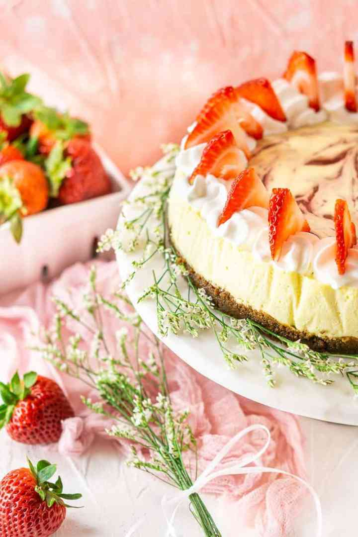 The fresh strawberry-ginger cheesecake on a white marble cake stand with white flowers around it.