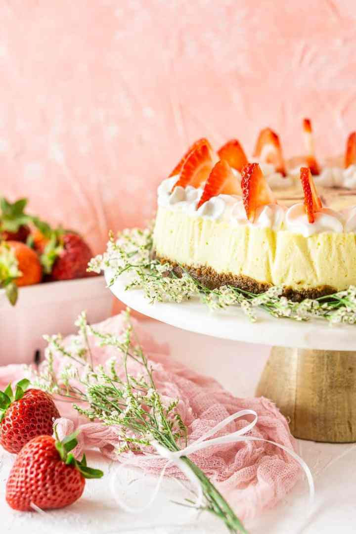 The fresh strawberry-ginger cheesecake on a marble cake platter with flowers and strawberries around it.