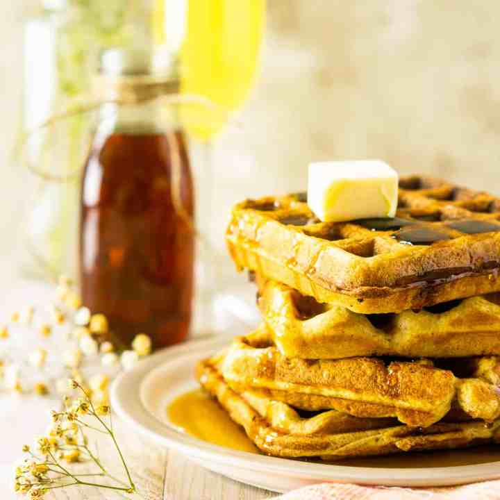 A stack of perfect buttermilk waffles with baby's breath flowers, syrup and a mimosa.