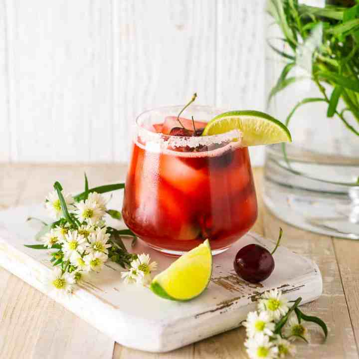 A fresh cherry margarita on a white wooden board with white flowers in a vase in the background.