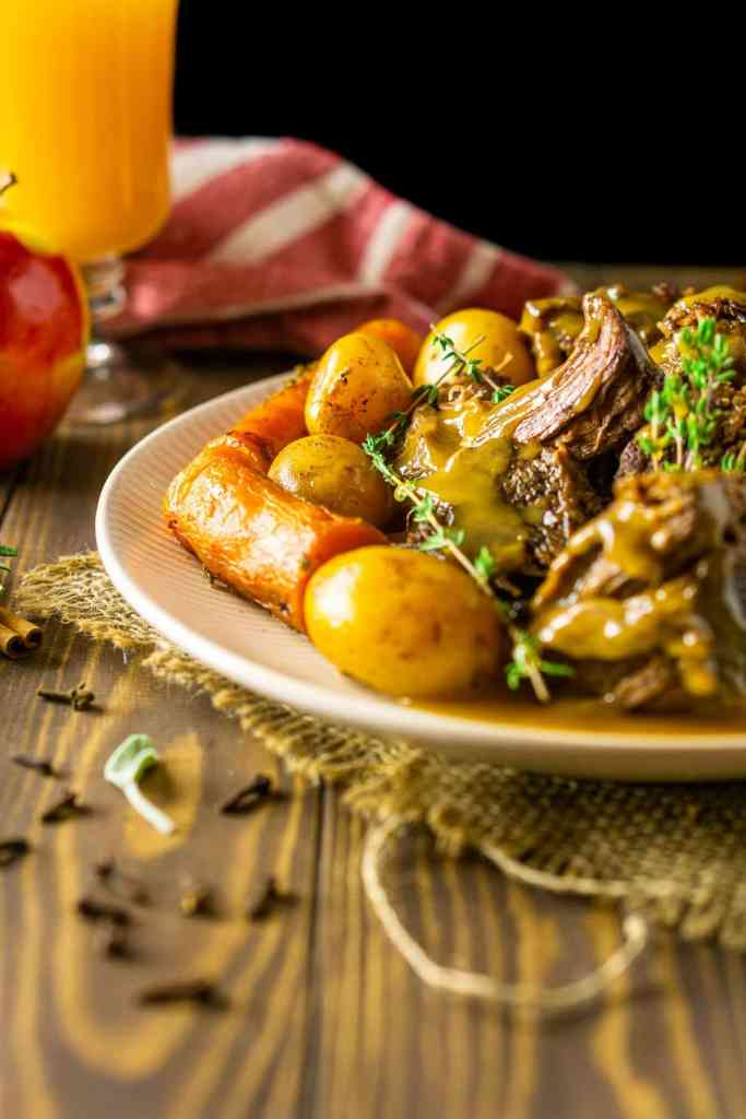 Apple cider pot roast on a plate sitting on burlap with whole cloves and fresh herbs.