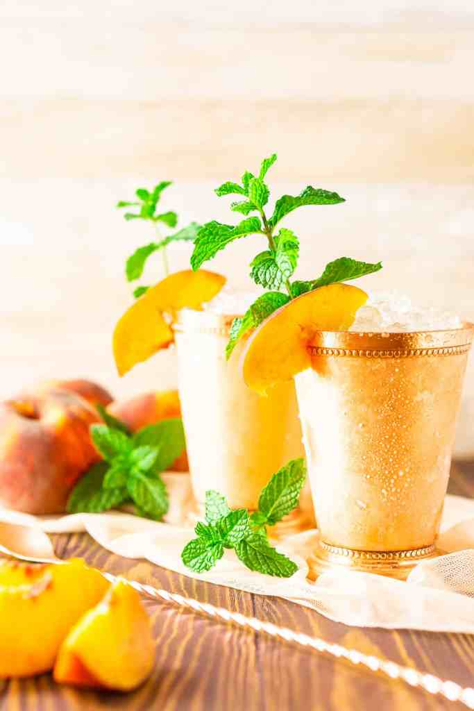 Two brown sugar-peach mint juleps with a bar spoon and peach slices next to them.