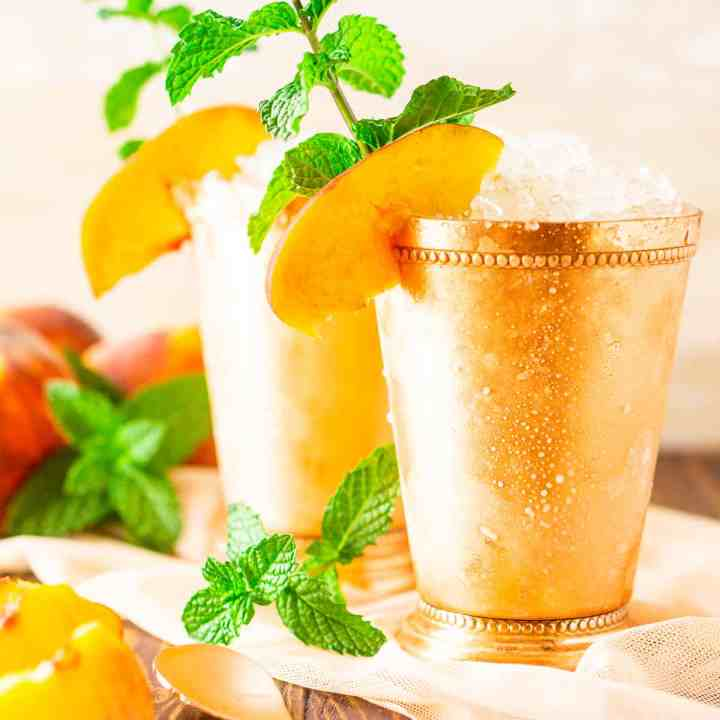 Two brown sugar-peach mint juleps with fresh mint sprigs and peach slices on the side.