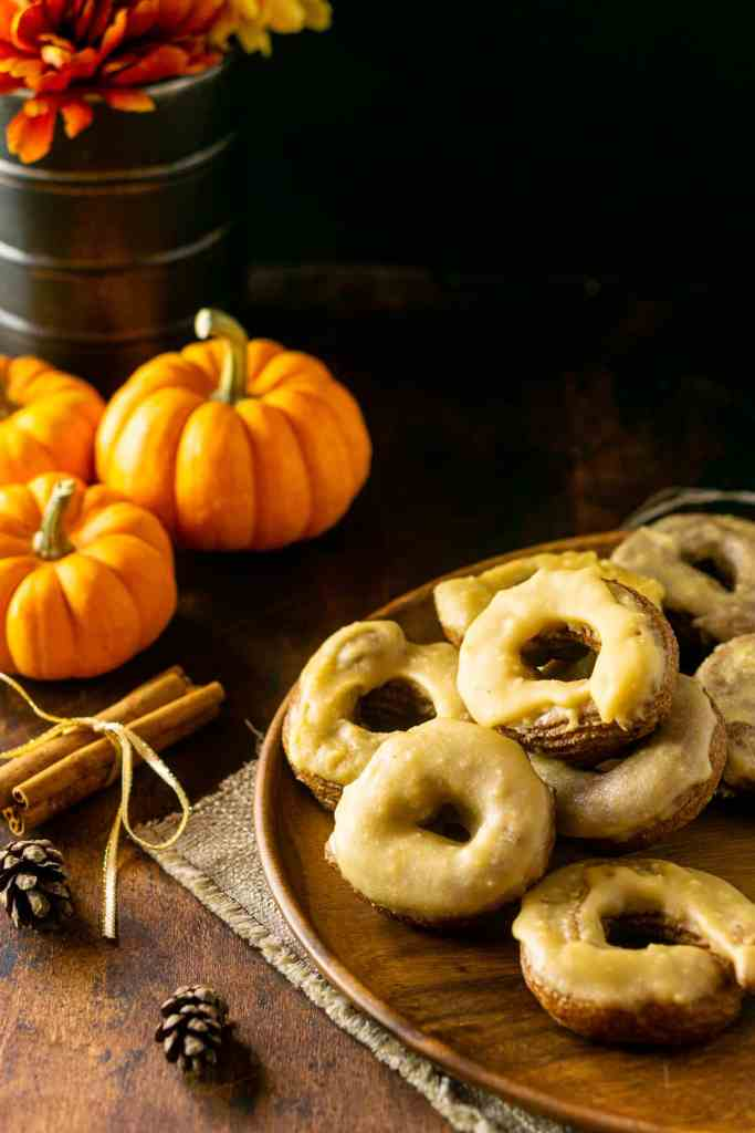 Pumpkin crullers on a wooden plate and fall-colored fabric.
