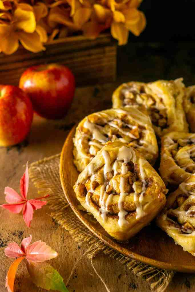 Looking down on a plate of apple cinnamon rolls with apples and leaves to the side.