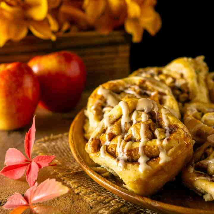 A plate of apple cinnamon rolls on burlap with fall leaves and flowers in the background.