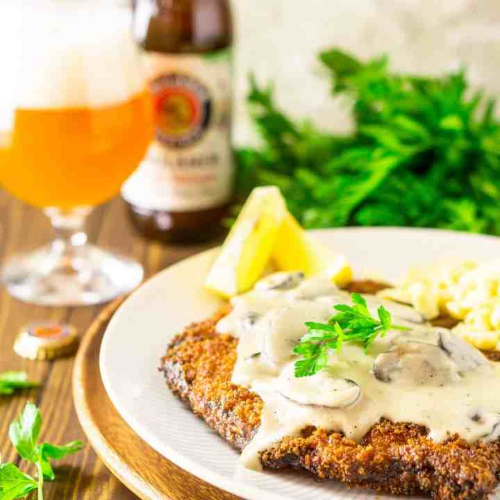 The beer-brined schnitzel topped with creamy mushroom gravy with a bunch of fresh parsley and a hefeweizen in the background.