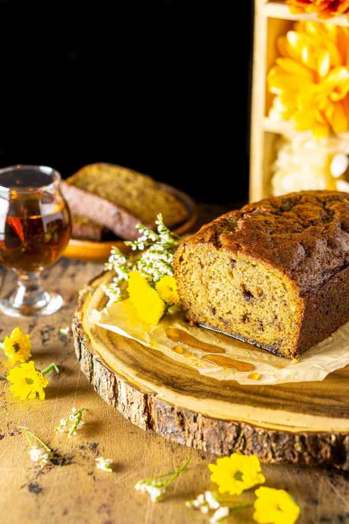 A loaf of this boozy banana bread with a glass of bourbon behind it and flowers to the side.