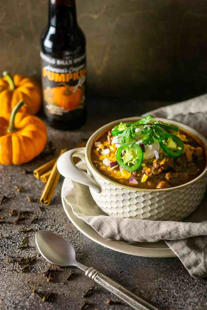 Looking down onto a bowl of pumpkin and chorizo chili with pumpkins to the left.