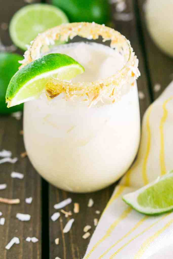 A coconut margarita with a yellow napkin and lime slices on the side with toasted coconut scattered around it.
