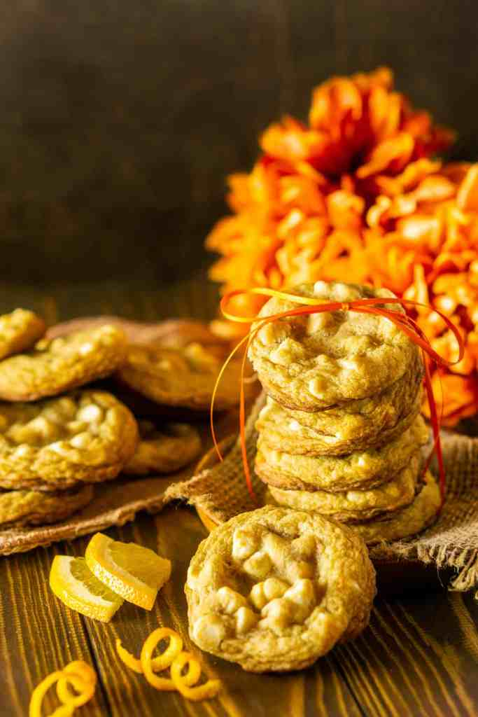 A stack of ginger-maple cookies with a bunch of orange flowers behind it and a couple orange zest twists on the side.
