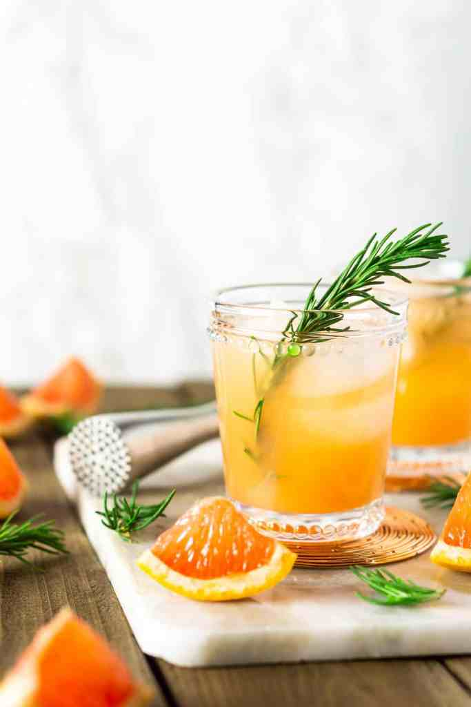 Two rosemary-grapefruit spritzers with a white marble background.