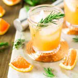 A rosemary-grapefruit spritzer from the front and top on a marble tray.