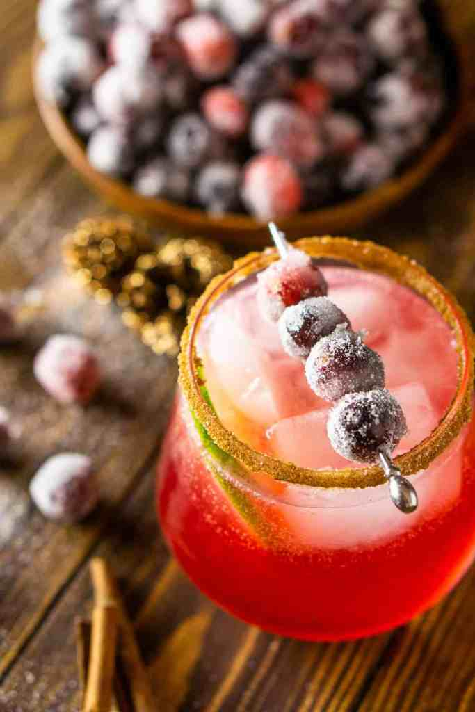 A close-up view of a cranberry holiday margarita with a sugared cranberry garnish on top.