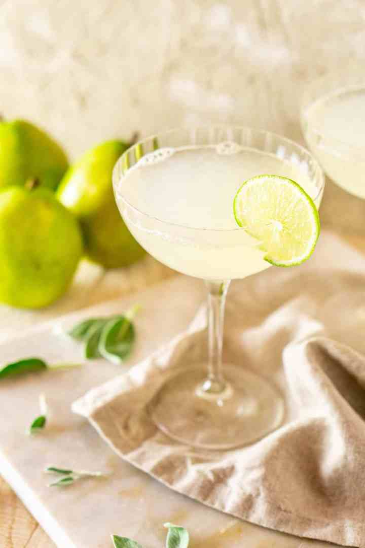 One pear-sage gimlet on a neutral-colored napkin and white marble board.