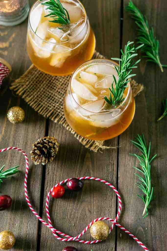 An aerial view of two chai bourbon smashes with Christmas string and rosemary around them.