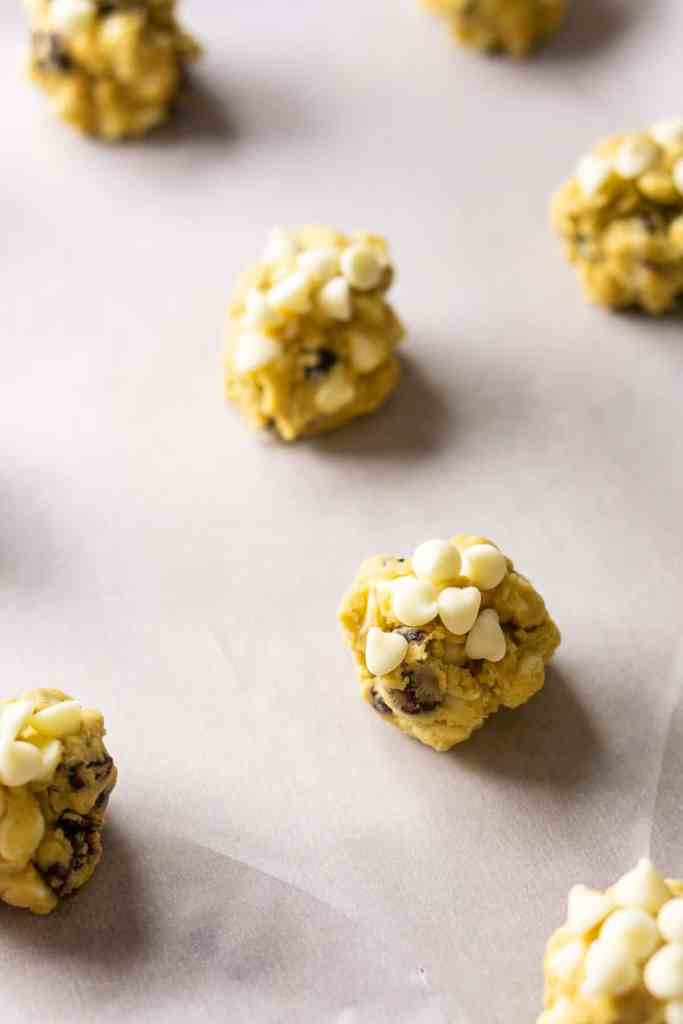The cookie dough shaped into balls on a parchment paper-lined baking sheet.