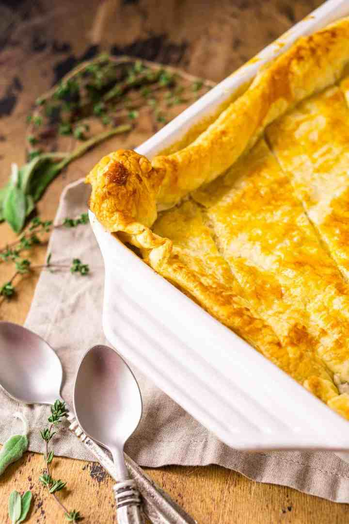 The baked chicken and mushroom pie on a napkin with spoons and herbs to the side.