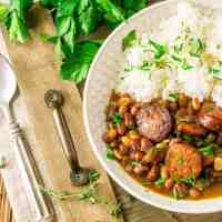 A bowl of Instant Pot red beans and rice on a wooden tray with a bunch of parsley in the background and a spoon to the side.