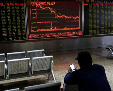 An investor sits in front of displays showing stock information at a brokerage office in Beijing, China October 11, 2018. REUTERS/Thomas Peter