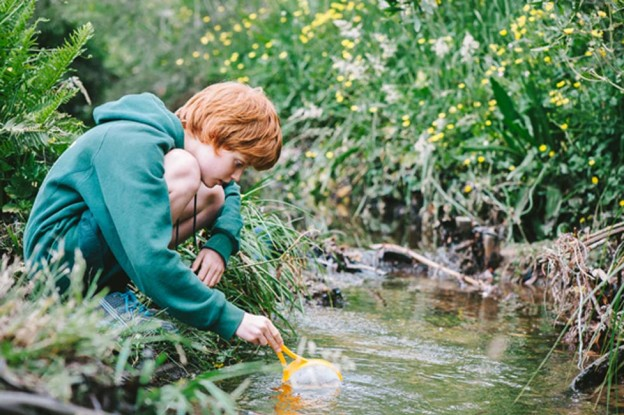 Student catching water creatures