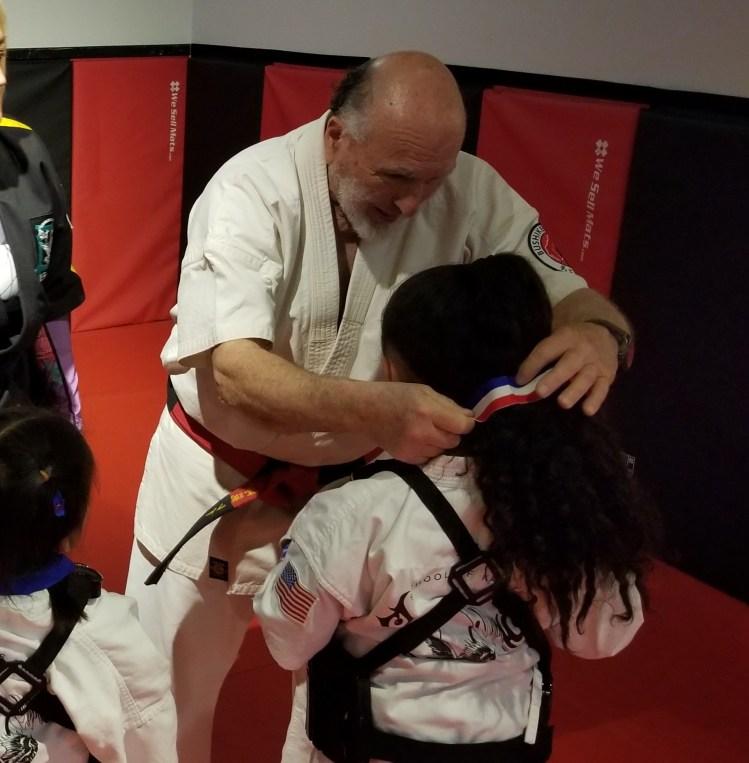 karate elder helps younger student
