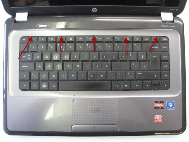 Turn laptop over and remove keyboard. The arrows point to small clips that hold in keyboard which need pushing back