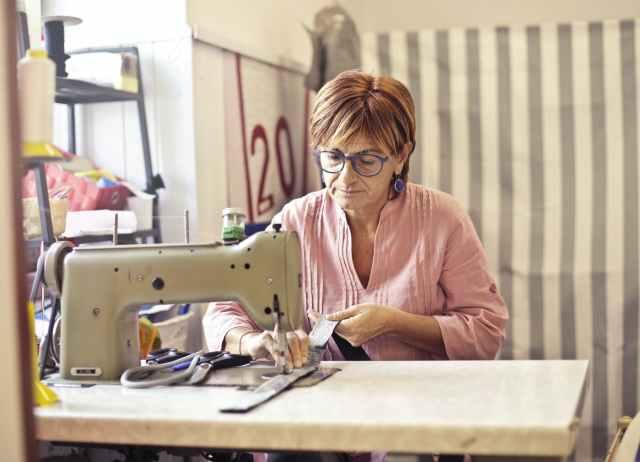 photo of woman using sewing machine