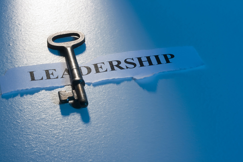 """A key laying on a piece of paper with the word """"leadership"""" on it."""