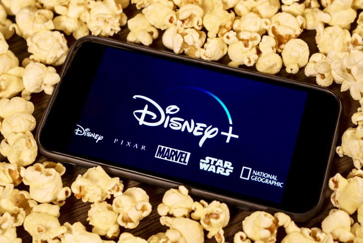 Grand Prairie, TX/USA - Aug 2019: Disney Plus on smartphone with popcorn. Dinsey+ is a new streaming subscription service that will feature Marvel, Pixar, Star Wars, and National Geographic content