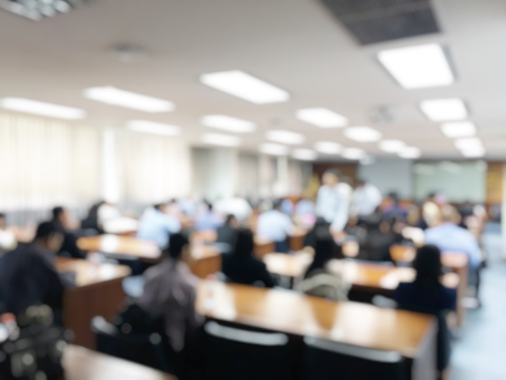 Blurred image of business people and student sitting in conference room or meeting room for profession seminar with screen projector for showing information, education or training concept.