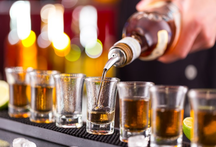 Barman pouring hard spirit into glasses in detail alcohol