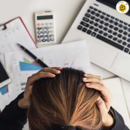Girl stressed out at her desk with hands on her head