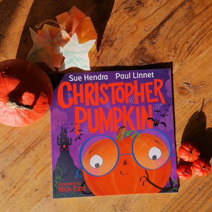 Christopher Pumpkin Book with pumpkins and lanterns on a wooden table