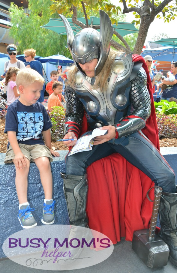 No more boring lines at Disneyland - grab our 2016 'Unofficial' Disneyland Activity & Autograph book to keep the kids happily entertained! Thor playing games in our activity book with boy at Disneyland